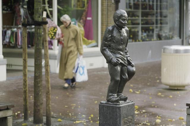 """TLB023000229_002 - De kruikenzeiker is een beeld van een textielarbeider met een wat afgetobt gelaat en een bolle kruik in de hand, op stenen sokkel. Op de sokkel een plaat met de tekst: """"Aangeboden aan de kruikinnen en kruiken ter gelegenheid van """"tweekirelluf (2keer11) kruikenstad 1986"""" Carnavalsstichting Tilburg"""". """"Sokkel aangeboden door Het Nieuwsblad Dagblad voor Midden-Brabant"""". Het beeld is gesigneerd JM (achter linkervoet) en H.S. (achter rechtervoet). Het beeld is ontworpen door Henk Smulders (1925-1994), beeldend kunstenaar te Tilburg, o.a. werkzaam voor de Efteling. Het beeld is vervaardigd in opdracht van de Carnavalsstichting Tilburg bij gelegenheid van de viering van 'Tweekirelluf Kruikenstad' in 1986. De kruikezeiker, een verwijzing naar het textielverleden van de stad, is van oudsher het symbool van Tilburg in carnavalstijd. Maar naast de oude vertrouwde miniatuurbeeldjes van gips, beschikt de stad nu ook over dit meer 'volwassen' en duurzaam exemplaar. Het gebruik van de naam Kruikenzeiker komt voort uit het gebruik van urine bij enkele bewerkingen van de wol. Vroeger werd urine gebruikt bij het vollen, het wassen en het verven. Dat gebeurde niet alleen in Tilburg, maar overal waar lakens of wollen stoffen werden gefabriceerd. Bij het vollen werd 'bedorven urine' als reinigings- en glijmiddel gebruikt, bij het wassen was de urine eveneens een reinigingsmiddel, en bij het verven van wol bevorderde de urine het gelijkmatig verdelen van de verf. Arbeiders die hun urine kwamen inleveren kregen daarvoor betaald. De urine werd in kruiken meegenomen naar de fabriek. Zo ontstond de naam Kruikenzeiker. Met de komst van chemicaliën bleek de urine niet meer nodig te zijn en verdween de kruik langzaam uit het straatbeeld. Maar de naam die bleef."""