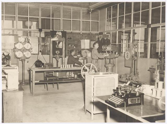 038950 - Volt. Zuid. Chemische Afdeling. De afdeling Materiaalkeuring in september 1948. Deze afdeling was gesitueerd naast het Chemisch Lab. in gebouw M noordzijde op het bordes van de gereedschapmakerij. (Van gloeilamp tot hoogspanningstrafo bldz.40) In de hoek staand Dhr. Herman Scheirs en zittend Jo Dankers. Voltstraat heette toen Nieuwe Goirleseweg.