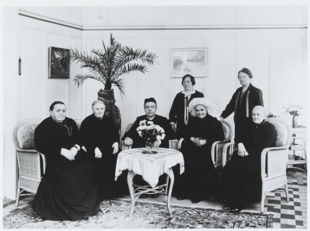 056197 - De St. Elisabethvereniging te Goirle in 1927, gefotografeerd in de serre van de familie Peijnenborg-Hamers aan de Tilburgseweg 33. Zittend v.l.n.r. Jans Anssems, Piet Hamers-van Erven, pastoor Peters, Hanmarie Spapens-de Gruijter (met Brabantse poffer) en Sjo van Besouw-Smulders. Staande links Anna Peijnenborg-Hamers, rechts Jo van Heeswijk-Leenaarts.