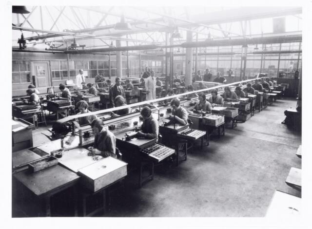 038535 - Volt. Zuid. Fabricage. Productie. Het solderen van condensatoren in 1933 in de shedbouw C aan de Voltstraat ( toen Nieuwe Goirleseweg ). De heer achter links met witte stofjas is Dhr.Lammens destijds afd.Chef van deze afdeling. Die in het midden met lichte stofjas is Dhr. van Peer, toen en tot zeker 1965 baas in de afdeling. Foto uit gedenkboek afscheid van Dhr. Anninga directeur.