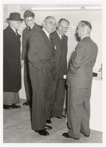 038917 - Volt. Zuid. Tentoonstelling van de Volt vakliedenopleiding april 1957 in de kantine aan de Voltstraat. De drie rechtse bezoekers zijn v.r.n.l. Dhr.van Gorp, oud afd.chef van de gereedschapmakerij, Dhr. Hopstaken, praktijkdocent vakliedenopleiding en Dhr. Lap, directeur Philips bedrijfsschool.