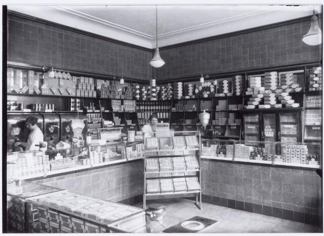 049859 - Winkels. Links Bertha Mutsaers. Zij was van 1934 tot 1935 hoofdjuffrouw van dit filiaal.  Foto uit ´Je Taalboek´ van frater Victor van Nispen. Interieur van het filiaal van de firma P. de Gruyter & Zn. aan de Gasthuisstraat 9a.