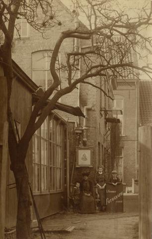 650398 - Schmidlin. De familie Schmidlin naast het atelier aan de Gasthuisstraat. V.l.n.r. Louis Jr.,Johanna Schmidlin-Dubois, Lies en Karel. Louis Sr. fotografeerde ook zichzelf via een crayonportret aan de muur. Geheel links de ramen van de fotostudio, gericht op het noorderlichtom de lichtinval constant te kunnen  houden. 1912.