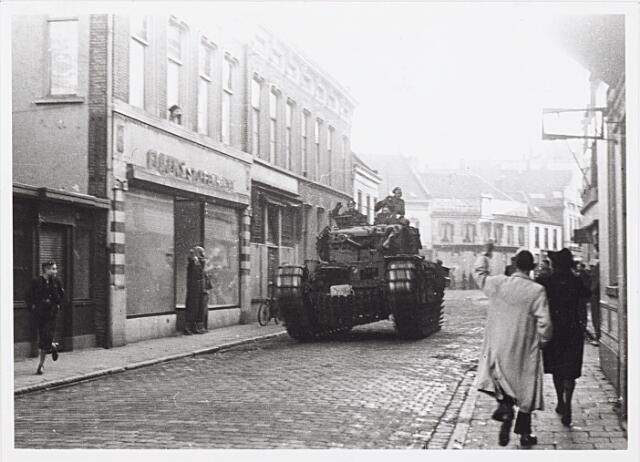012234 - WO2 ; WOII ; Tweede Wereldoorlog. Bevrijding. Een Britse tank dendert door de Zomerstraat. De etalage van stoffenhandel Eijkens (links) is leeg