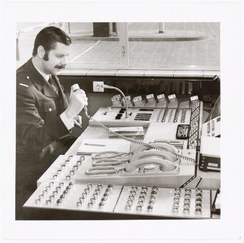 039308 - Volt, Hulpafdelingen, Portiers, Bewaking. De nieuwe bewakingsloge van complex Volt Noord, in gebruik sinds 1961, met bewakingsbeambte Reijnhout. De nieuwe beveiligingsdesk was een hypermodern stukje techniek.
