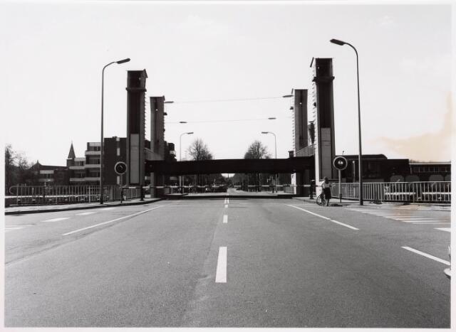 034821 - Hefbrug over het Wilhelminakanaal, gezien in de richting van het centrum. Links de toren van de Sacramentskerk en rechts houthandel Key