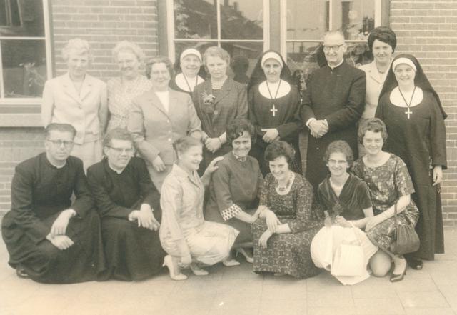 651612 - Meisjesschool Vincentius. Tilburg. Een groepsfoto van het personeel in 1961. Van links naar rechts, staande, mw. Jacobs (plv. mej. Snoeren), mw. Houtsma (plv. mw. v.d.Wee-Meynckens), mej. Vriens, Zr. M. Cornela (plv. Zr. M. Emmanuel), mej. Meijs, Zr. M. Alix, z.e.h. pastoor Martin, mw. van Eijck en Zr. M. Sybilla.  Zittend van links naar rechts w.e.h.kapelaan Ligtvoet, w.e.h. kapelaan van Vroonhoven, mej. v.d. Zanden, mej. Wittens, mej. Langenhoff, mej. Roothans en mej. Kafoe.