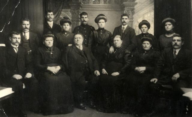 """092264 - Het gezin van Cornelis Cools (Udenhout 1851-Tilburg 1937) en Maria Catharina van Akkerveeken (´s-Hertogenbosch 1853-Tilburg 1928) uit de Akkerstraat 36 te Tilburg. Cornelis Cools was fabriekarbeider in Tilburg totdat hij rond 1873 zijn rechterarm verloor bij een fabrieksongeval. Vanaf die tijd luidde zijn bijnaam """"Kees d´n eenarm"""". Zittend van links naar rechts; Alphonsus F. Cools(1884-1938) gehuwd met Antonia M. Spijkers, Adriana J.M. Cools (1877-1947) gehuwd met voerman Josephus van Gorp, Cornelis (Kees) Cools, Maria C. (Mie) van Akkerveeken, oudste dochter Petronella J.J. Cools (1873-1946) gehuwd met wever Martinus C. Broers, oudste zoon Johannes Cools (1874-1958) gehuwd met Maria H. Hobbelen. Staand van links naar rechts; Henricus L. Cools (1882-1972) gehuwd met Cornelia A. Somers, Vincentius H. Cools (1876-1952) gehuwd met Josepha M. van Oosterhout, Gerdina J.M. Cools (1890-1975) gehuwd met wolmaler Johannes H. de Rooij, Antonius M. Cools (1888-1960) gehuwd met Wilhelmina C. van Opheusden, Cornelia P. Cools (1893-1954) gehuwd met wolmaler en groentenhandelaar Cornelius W. Broers, Franciscus C. Cools (1886-1965) ongehuwd, Joanna M.J. Cools (1879-1960) gehuwd met wollenstoffenwever C.H.J. Oerlemans en Joannes C. Bertens, Petronella C.A.M. Cools (1892-1973) gehuwd met duivelaar Josephus A.M. Laurijssen. De foto werd waarschijnlijk ter gelegenheid van het eerste verlof van Antonius Maria Cools (Toon) uit Nederlands-Indië. Toon ging in 1906 in dienst van het Koninklijk Nederlandsch Inidisch Leger (KNIL). Via de Waalkazerne te Nijmegen vertrok hij naar de Oost. In 1912 kwam hij voor korte tijd terug naar Nederland en verbleef daarna nog minstens 6 jaar in Indië."""