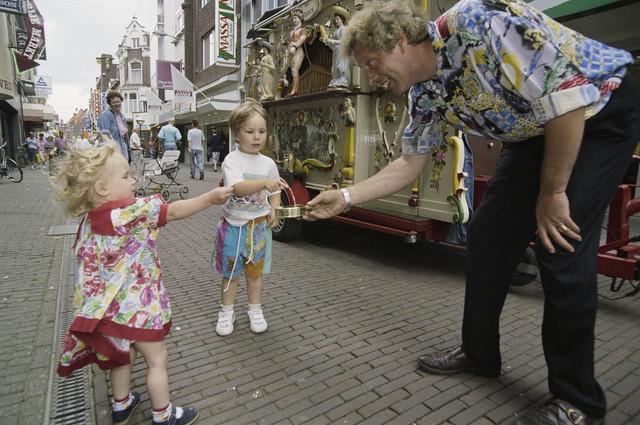 TLB023000531_001 - Kinderen geven geld aan de orgelman in de Heuvelstraat.