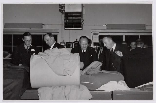 037681 - Textielindustrie. Vol belangstelling luistert prins Bernhard naar de uitleg van directeur Hein Enneking sr. van wollenstoffenfabriek H. F. C. Enneking aan de Goirkestraat dat hij op 13 november 1950 bezocht