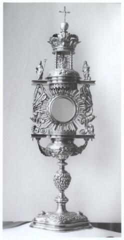 019617 - Kunstschatten; kerkschatten.  Monstrans van de parochie St. Dionysius (Goirkesekerk) uit 1661. In het midden een kapelletje met Maria en het Christusbeeld,  links een beeldje van de heilige Norbertus en rechts Augustinus. Het is van verguld zilver en bevat het stadsteken van Antwerpen. Aan de onderkant staat een inscriptie: Ecclesia Tilburgensis in Steenvoort anno 1661, een verwijzing naar de grenskerk in Steenvoort, een gehucht onder Poppel