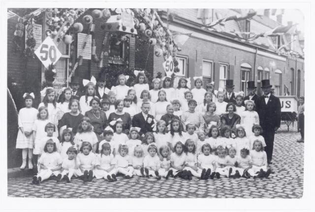 039842 - Gouden bruiloft in de Boomstraat in 1924. Op 23 juli trouwde te Tilburg Hendrikus van Beurden (1850-1931) met Gerardina van Iersel geboren 1854. De bruidegom was fabrieksarbeider en zoon van Niclaas van Beurden en van Johanna Maria Van Beurden-Smits. Het echtpaar woonde in de Boomstraat nr. 64. Door de buurtbewoners werd een feest-damescomité. Op de foto het gouden paar met 54 bruidjes, de heren van het feestcomité: A. van Trier (voorzitter), A. van de Ven, H. Piëtte, D. Knibbeler en P. Kwaaitaal. Het damescomité: de dames Van Trier, De Beer, Wouters, De Zwart en Van Rijsewijk. De werkgever van H. van Beurden, de firma Mommers aan de Goirkestraat, had ter gelegenheid van het feest een auto beschikbaar gesteld.
