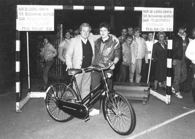 800109 - Sport. Voetbal. Voetbalvereniging R.K.S.V. Taxandria in Oisterwijk. Loterij. De fiets is beschikbaar gesteld door Rijwielhandel Rien van Amelsvoort. De kist door meubelfabriek Oisterwijk.