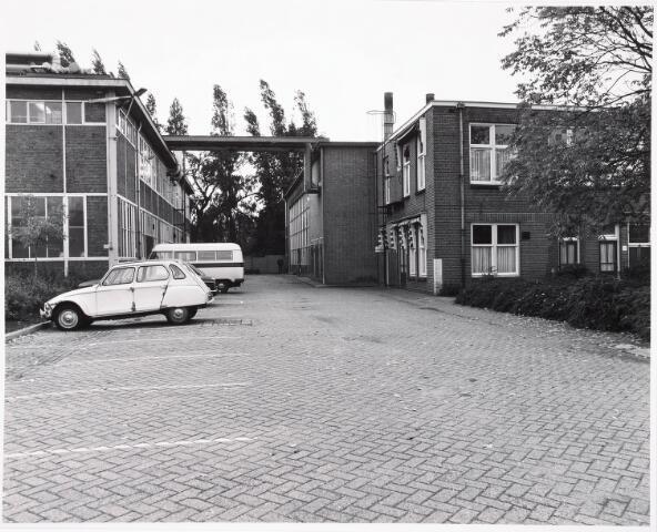 034140 - Binnenplaats van Volt parallel aan de Voltstraat in westelijke richting. De bomen op de achtergrond stonden in de tuin van het klooster AVÉ MARIA.Het gebouw links is een gedeelte van de in 1929 gebouwde gereedschapmakerij. Bij het busje was de ingang. Het achterste gebouw rechts is het in 1961 gebouwde nieuwe oliegestookte ketelhuis.Op die plek zat van 1919 tot 1929 de gereedschapmakerij ( machinefabriek ) en van 1928 tot 1961 de hardeij en de fitterij. Het voorste gebouw rechts was beneden medische dienst ook wel genoemd verbandkamer. De bovenverdieping diende als leslokaal.