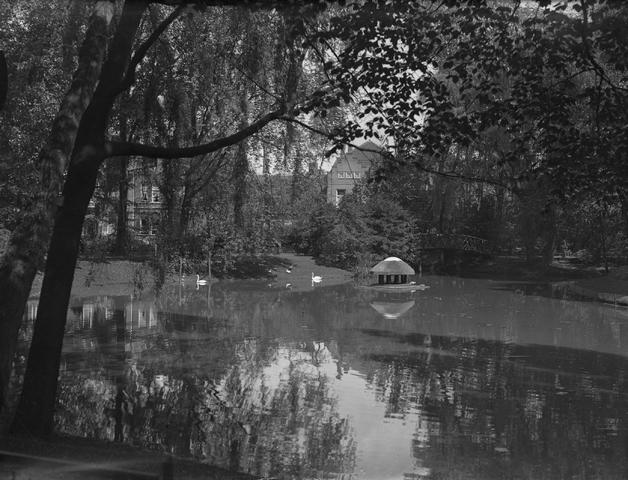 652155-bew - De vijver in het Wilhelminapark. Het Wilhelminapark met zicht op de Noordzijde. Op achterzijde het brugje met in het water een eenden overkapping waar ze zich kunnen vertoeven.