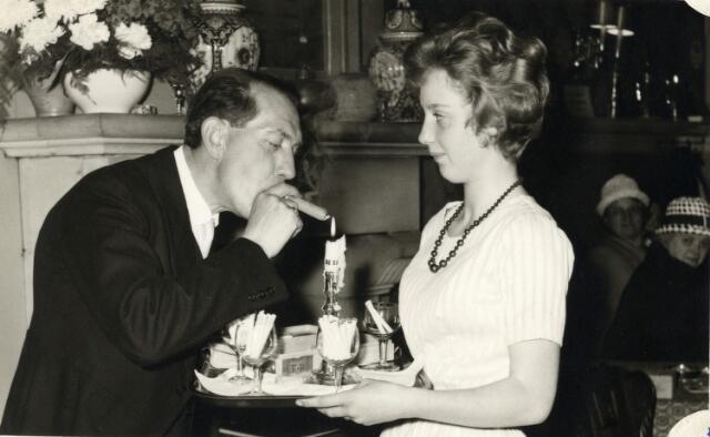 093044 - Een foto uit de tijd dat er nog sigaren en sigaretten gepresenteerd werden tijdens een receptie. Melkhandelaar Dré Smulders met zijn dochter tijdens de receptie, gegeven t.g.v. de viering van het 25-jarig bestaan van de R.K. Bond van Melkhandelaren St. Martinus.