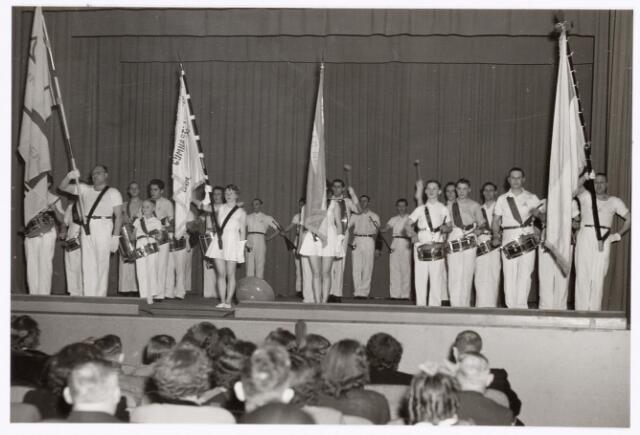 """038819 - Volt. Sport en ontspanning. De drumband van Gymn. & Atl. Ver. Volt tijdens de jaarlijkse uitvoering van de gymnastiekvereniging in 1951 of 1952. Plaats, de """"Metropole"""" Schouwburg aan de Heuvel. Enige tijd nadien is deze drumband toegevoegd aan harmonie Volt.  De linkse vlaggendrager is André Donders. Vlaggendraagster 2e van links is Mientje Pijnenburg. De kleinste tamboer is Jan Vermeulen, zoon van de voorzitter."""