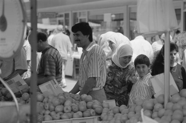 TLB023000419_001 - Mensen van allochtone afkomst bij een fruitkraam op de weekmarkt.