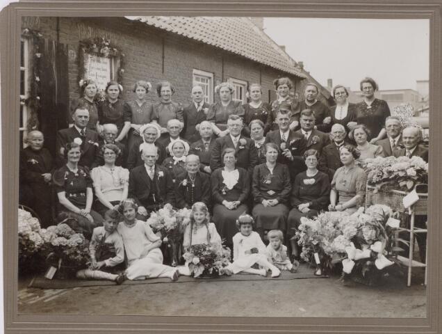 650416 - Schmidlin. Aan de Vernisstraat 53 (huidige Surinamestraat) vierden Cornelus Laurijssen, wolwasser geboren te Tilburg op 5-5-1867 en Maria Catherina van Puijfelik geboren te Tilburg 22-6-1862 hun gouden bruiloft. Zij trouwden in Tilburg op 2-5-1889.  Kees en Mieke staan afgebeeld op een sigarenbandje.Dit was vroeger tamelijk gangbaar.Kees werkte als wolwasser bij Jan Pessers aan de van Bylandtstraat. Zittend op de voorgrond met pijpekrullen kleindochter Tony Weijters.Vlak achter het gouden bruidspaar staat (met muts) Betje Laurijssen, zij was voorbidster in de Hasseltse kapel.Links achter haar met muts staat Marie Laurijssen. Helemaal rechts achteraan Annie Neve-Spijkers (kokkin op de bruiloft).Tweede vrouw rechts van de gouden bruid schoondochter Marie Damen.Staande achter haar,met sigaar, haar man Willem Laurijssen.Rechts van de gouden bruid, dochter Mieke Laurijssen achter haar haar man, Toon van Loon oudoom van Noud van Loon (fietsenspeciaalzaak)
