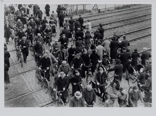037215 - Spoorwegovergang. Fietsers. Met de fiets aan de hand steken mannen en vrouwen op weg naar hun werk de spoorweg over.