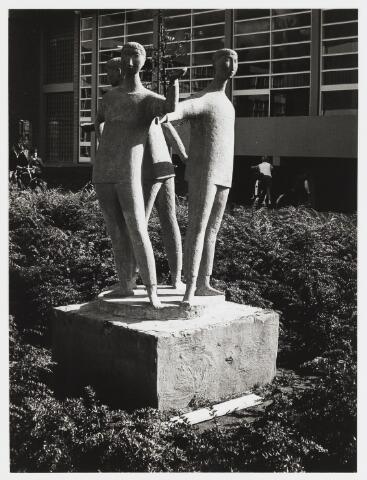 """067665 - DRIE KINDEREN IN EEN KRING. Beeldengroep in edelbeton van de Tilburgse kunstenaar Hans CLAESEN (1925-1995). Lokatie: plantsoen van voormalige R.K. Basisschool """"Gemma Galgani"""" / """"Albertus Magnus"""" aan de Postelse Hoeflaan 330. Realisatie: 1962. De figuren vormen weliswaar een kring, maar ze staan met de ruggen naar elkaar toe en lijken van elkaars bestaan niet op de hoogte. Door de balletachtige houdingen en """"onleesbare""""gelaatsuitdrukkingen, lijkt de groep zich aan de werkelijkheid te onttrekken, als een droombeeld.    Trefwoorden: Kunst in de openbare ruimte.Onderwijs."""