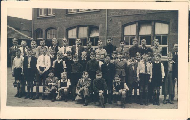 651838 - Tilburg. Leerlingen van de Rooms Katholieke jongens lagere school (basisschool) Heilig-Hart van Jezus in de parochie Noordhoek. Op de achtergrond een deel van het schoolgebouw.