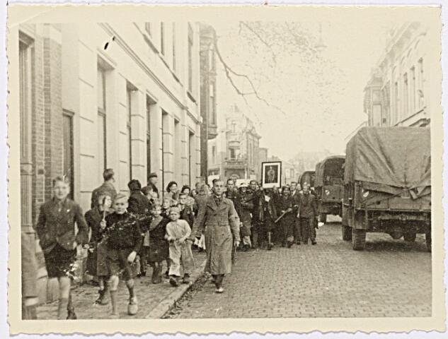 012303 - WO2 ; WOII ; Tweede Wereldoorlog. Een NSB'er wordt tijdens zijn arrestatie nog eens extra vernederd doordat hij een portret van Hitler met zich mee moet dragen
