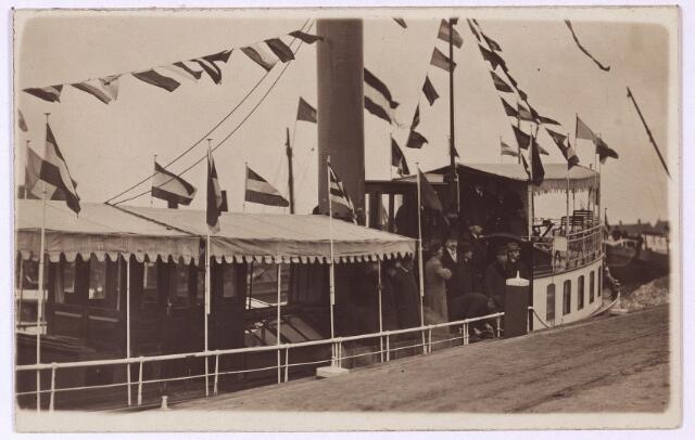 002740 - Op 28 april 1919 werd het traject Oosterhout-Tilburg van het Wilhelminakanaal officieel geopend. 's-Morgens vertrokken het college van B. & W., de raadsleden en andere hoogwaardigheidsbekleders met de tram van Tilburg naar Oosterhout, waar een lunch werd aangeboden in café-restaurant de Koppelpaarden door Rijkswaterstraat. Daarna vertrok het gezelschap op twee stoomboten naar Tilburg, waar de feestelijke versierde schepen aanlegden bij de losplaats aan het Lijnsheike. Met een dertigtal auto's gingen de genodigden vandaar naar het gemeentehuis, waar de feestelijkheden werden voortgezet. De foto werd genomen bij de loswal aan het Lijnsheike.