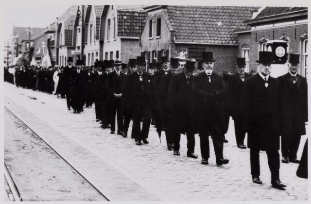 084374 - Leden van de gemeenteraad gefotografeerd in de Doelenstraat in de begrafenisstoet van pastoor Andreas van Beijnen.