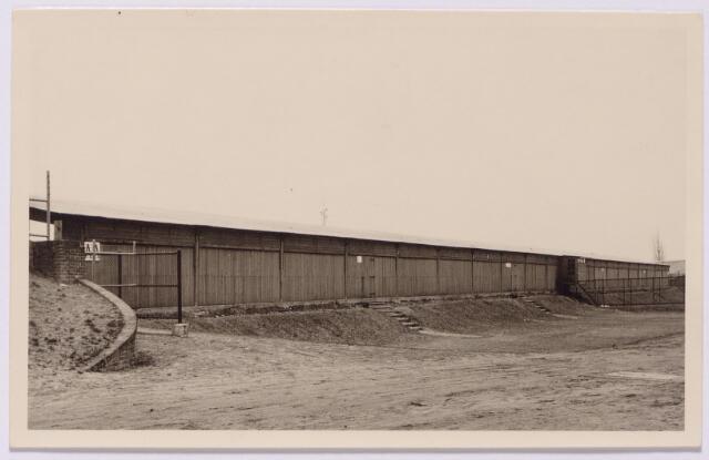 """043438 - Buitenzijde van de tribune van het oude sportpark aan de Goirleseweg. Tot de bouw van dit sportpark werd besloten in 1919. Na de vaststelling van de oprichtingingsstatuten in oktober 1919, volgde een maand later de oprichting van """"de vereniging tot stichting en instandhouding van een sportpark."""" Het sportpark werk geopend in 1921."""