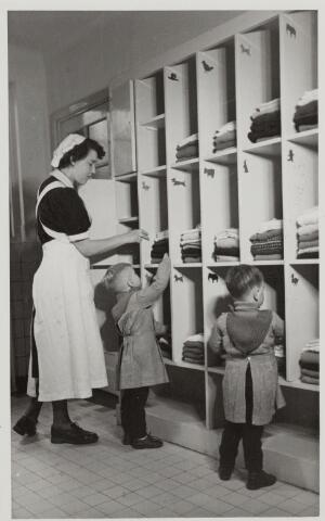 046365 - Medisch kinderdagverblijf Kleuterheil. Verpleegster met kleuters in de kleedkamer