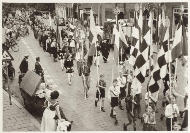 047341 - De nieuwe burgemeester, G.L. Elsen, werd ingehaald door afgevaardigden van alle Goirlese verenigingen en scholen. Op de foto de scholieren van de St. Thomasschool o.l.v. frater Bernulfus gefotografeerd op de Tilburgseweg.  Voorts, bakker De Jong (met kar) Kees en Huub Hoogendoorn, Huub Zilverberg, Willie v.d. Pol, Jan Scholten, Janus v.d. Wouw, Berrie van Ostaden, Wim Mallens met het portret van prins Bernard, Edie Brok, Kees van Kuyk en de Citroën van dokter Van Iersel.