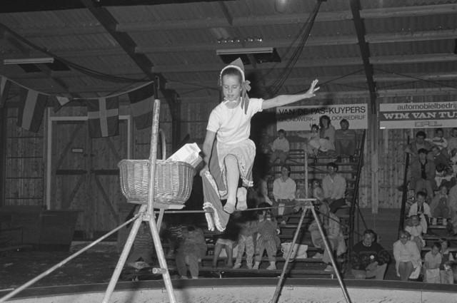 TLB023002532_003 - Een circus act, roodkapje op een dun stalen koord probeert bij de rietenmand te komen