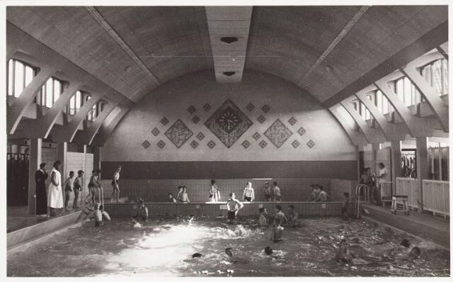 029969 - Zwembad aan de Ringbaan-Oost. Het tegeltableau inclusief klok op de binnengevel is ontworpen door kunstenaar Kees Mandos (1913-).