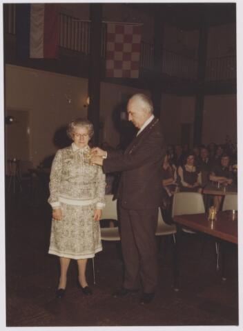 081341 - Afscheid van mevr. M. Aarts-Hobbelen (tante Miet) van de huishoudelijke dienst. Hier wordt zij onderscheiden met de eremedaille in zilver in de Orde van Oranje-Nassau door burgemeester Ballings.