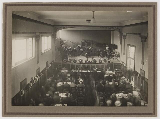 078643 - Feest vergadering vermoedelijk te Udenhout. Let op verzameling strohoeden langs linker wand.