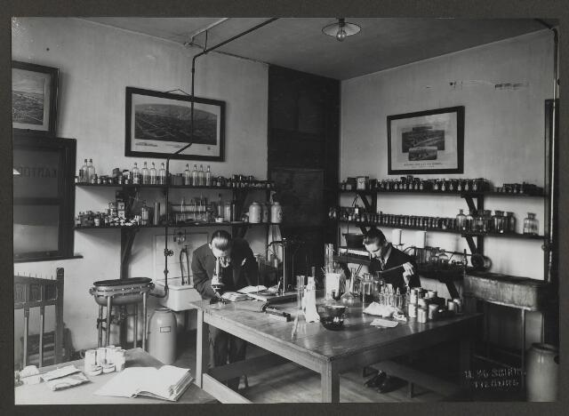 071868 - Het laboratorium en de laboranten (vermoedelijk Joop en Charles Janssen) van stoomververij en chemische wasserij De Regenboog aan de Bredaseweg. De foto is afkomstig uit een album dat werd gemaakt en aangeboden naar aanleiding van het 40-jarig jubileum van textielfabriek De Regenboog  van de firma Janssen en Bierens op 2 december 1930.