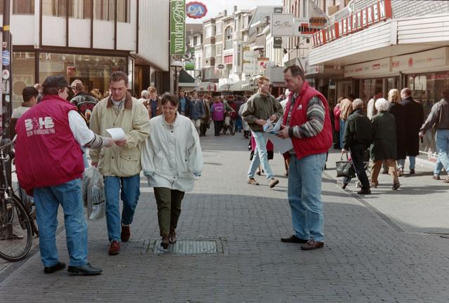 1237_001_044_018 - Staking van de CNV en FNV Bouw- en Houtbond voor een betere Bouw CAO in april 1995. Er worden folders uitgedeeld in een drukke Heuvelstraat.
