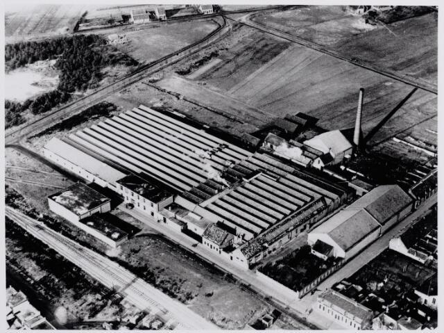 """046261 - De """"Tilburgsche Kamgaren en Wollenstoffenfabriek Tilkamwol"""" aan de Fabrieksstraat werd in 1937 gevestigd in de fabriek van de voormalige jutespinnerij. De Tilkamwol sloot op 15 maart 1968 haar poorten, waardoor ongeveer 200 werknemers werkeloos werden. Links op de voorgrond het goederenspoor van Goirle naar Riel. Rechts van de fabriek de Spinnerijstraat. Bovenaan de Nieuwkerksedijk."""