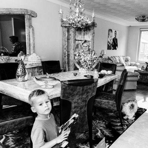 digi 1692_026 - Vrouw met kleinzoontje in de woonkamer van een woning in de wijk die in de volksmond bekend staat als de 'Vogeltjesbuurt'. De foto is onderdeel van een fotoserie van Anja van Eersel. Volksbuurt. Broekhoven. Groenewoud. Interieur.