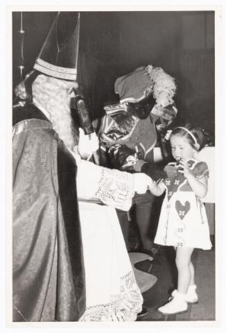 038872 - Volt. Zuid. Ontspanning. Viering Sint Nicolaas voor de kinderen van het personeel in 1959. Sint, Ab Haarlem, geeft een handje en Piet, Jos Spijkers, geeft wat te snoepen. Sinterklaas. St. Nicolaas
