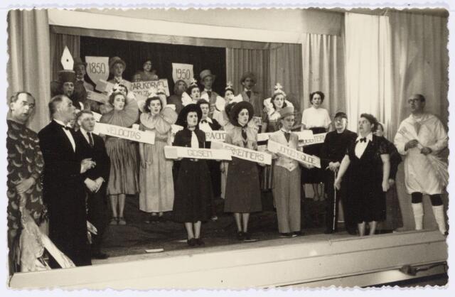 104020 - Toneel. Revue 'lo me nie lage'. Korvels prentenboek 1850-1950, opgevoerd t.g.v. het 100-jarig bestaan van de parochie Korvel. Slottableau. De vrouw rechts (met strikje) is dirigente Jo Reabel.