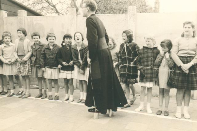 651623 - Meisjesschool Vincentius. Tilburg. Tijdens de sportdagen liet kapelaan van Vroonhoven zien dat hij echt de onbetwiste kampioen bliklopen op lange afstand is. Helaas werd het materiaal na afloop als onbruikbaar afgeschreven.  Op deze foto is duidelijk de 'mode' trant van de jaren 60 uit de vorige eeuw, te zien. Rokjes boven de knie, korte jasjes (of blazertjes) of vestjes, korte sokjes, nette schoentjes (geen sportschoenen) en korte haren of de haren in een vlecht. Kinderen waren toen echt kinderen en genoten van hun  jeugd. .