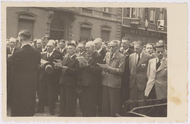 042734 - Nationale Feestdag na de bevrijding. Kranslegging  s middags om twaalf uur. St. Caeciliakoor onder leiding van Piet Raaijmakers. Op de achtergrond de winkel Witteveen.