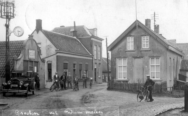 064884 - Dorpsstraat bij de klok. Deze heeft daar nog gehangen tot in de jaren 50.  De winkel links achter de groep mensen is van Freek de Visser.  In het huis waar Dingeman Driesprong voor staat woonde toen Jan van den Hoven.  Het hoge huis rechts naast de winkel was toen het postkantoor.  De weg rechts van het huis was de z.g. veerstoep; deze liep schuin af naar de haven welke een kleine honderd meter verder lag.  V.l.n.r.: ; N.N.  ; Bertus de Laat, de slager (met fiets) ; Elie Meywaard ; Sjaan Mustert ; N.N.  ; Kees Driesprong (met fiets   Dingeman Driesprong (waarschijnlijk) met fiets