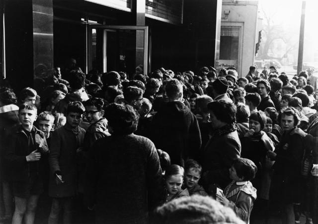 1238_F0212 - Groep kinderen met ouders.  Wachtend voor een gebouw, vermoedelijk een bioscoop.