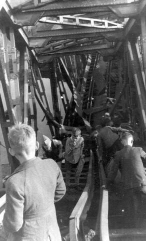 064691 - Tweede Wereldoorlog. Voetgangersverkeer op een verwoeste spoorbrug.