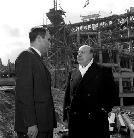 650671 - Schmidlin. Schouwburgdirecteur Wim Bary in gesprek met toneelgrootheid Albert van Dalsum. Op de achtergrond de Stadsschouwburg in aanbouw, april 1960.
