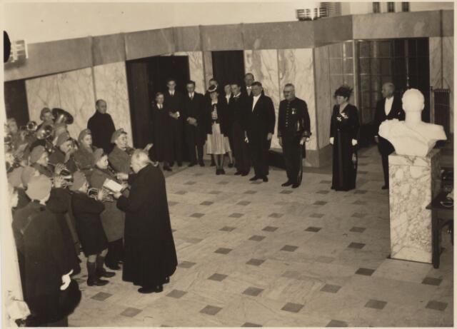 103383 - Aubade Huize Nazareth bij gelegenheid van de installatie van burgemeester mr. Jan C.A.M. van de Mortel. vlnr: fr. Placidius (J.M. de Visscher), fr. Leonard v.d. Voort, dr. Enneking van de Mortel, familie v.d. Mortel, burgemeester en mevr. v.d. Mortel-Houben, wethouder Scheidelaar. kinderaubade in paleis-raadhuis, vanwege barre kou en sneeuw in de hal 300 kinderen als afgevaardigden namens de 17000 schoolkinderen.