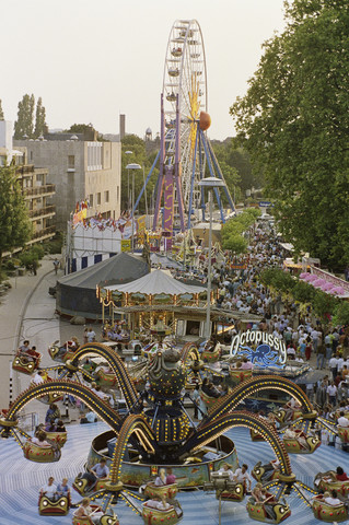 TLB023000204_001 - Overzichtsfoto Tilburgse Kermis met op de voorgrond de Octopussy en in het midden een Reuzenrad. Links op de foto het appartementencomplex de Frankenhof met rechts daarvan de Rechtbank.  De Tilburgse Kermis is de grootste kermis in de Benelux. Er staan jaarlijks tussen de 230 en 240 attracties uit binnen- en buitenland, in een 4,5 kilometer lang lint door het centrum van de stad. De kermis trekt jaarlijks meer dan een miljoen bezoekers en is daarmee een van de best bezochte evenementen van Nederland.